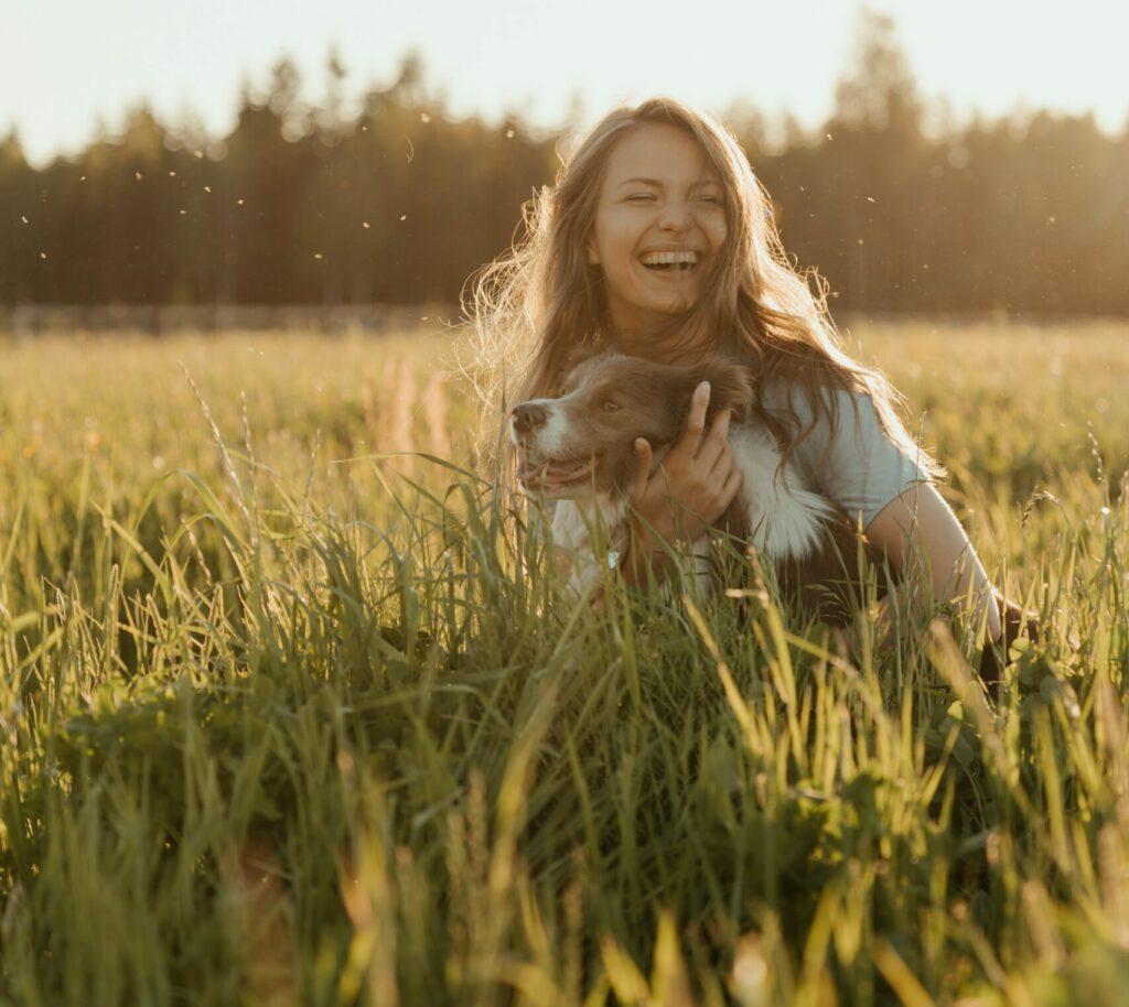 Människa och hund på ett fält i solnedgången.